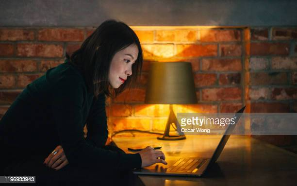 side view of cheerful young woman using laptop working at cafe - businesswoman stock pictures, royalty-free photos & images
