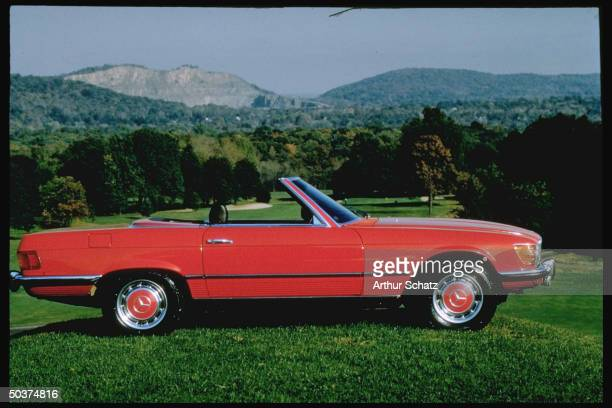 Side view of cherry red, mint condition Mercedes Benz on grassy lawn.