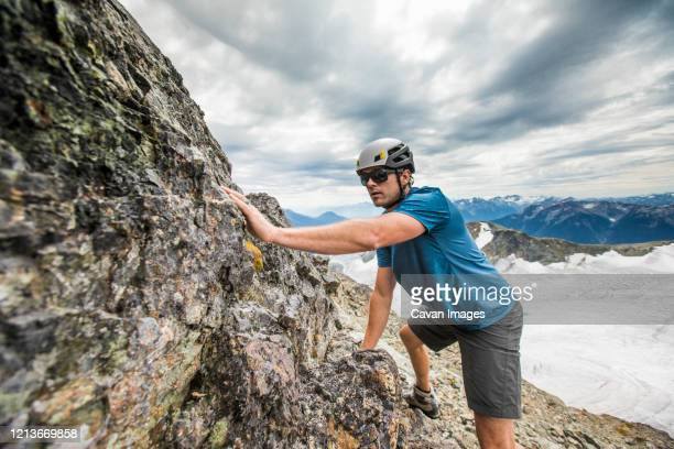 side view of climber scrambling up toward mountain summit. - スクランブリング ストックフォトと画像
