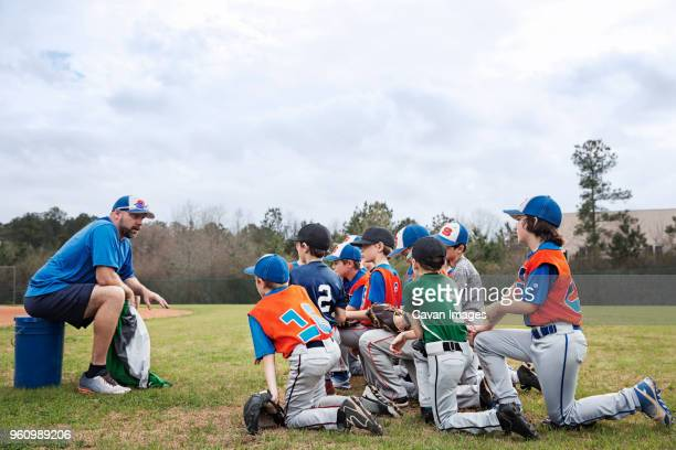 side view of coach talking to baseball team on field - little league stock pictures, royalty-free photos & images