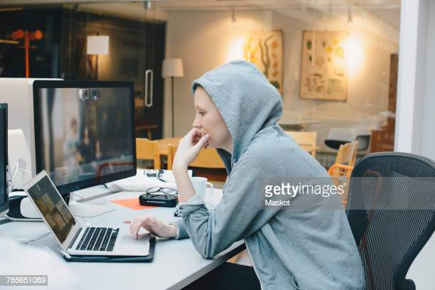 Side view of computer programmer using laptop at desk in office