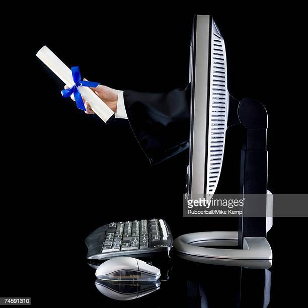 Side view of computer with hand coming through monitor holding diploma