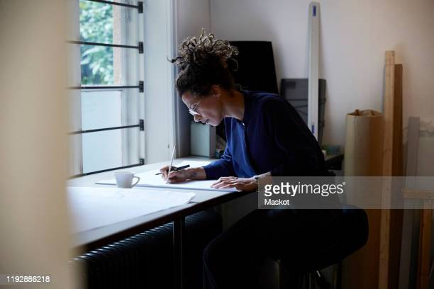 side view of confident female architect working in office - design professional stock pictures, royalty-free photos & images