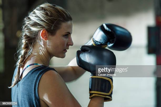 Side view of confident female boxer in gym