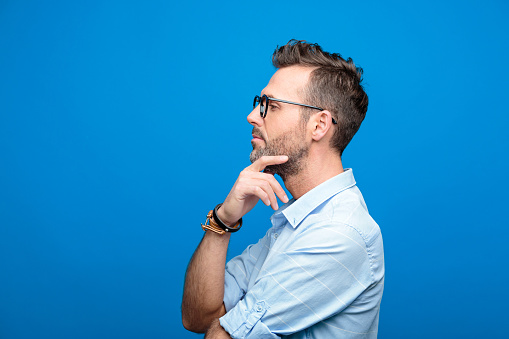 Side view of confident, handsome man, blue background 923616924