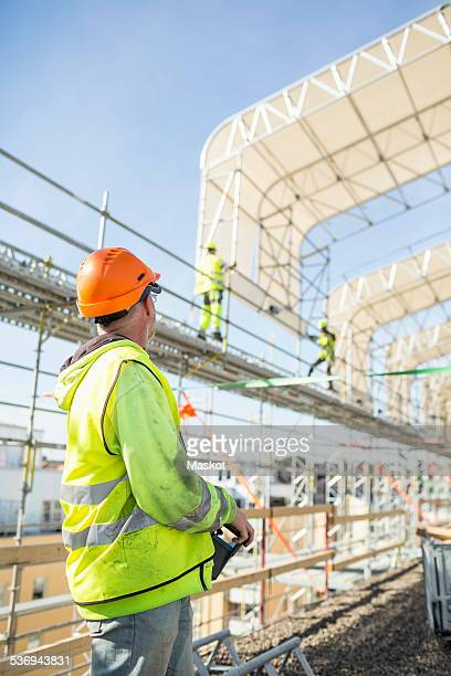 Side view of construction worker looking at colleagues working at site