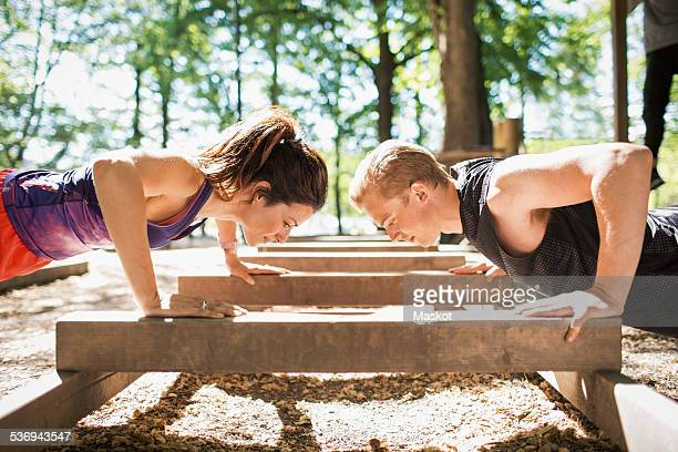 side view of couple doing push-ups at outdoor gym - krafttraining stock-fotos und bilder