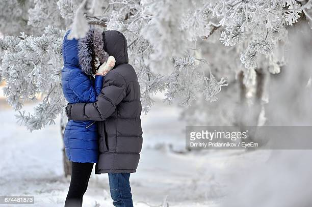 side view of couple hugging in the snow - winter coat stock pictures, royalty-free photos & images