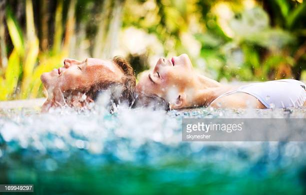 Side view of couple in the pool during tropical rain.