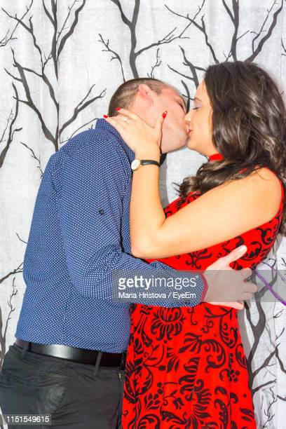 side view of couple kissing on mouth by wall at home - embrasser sur la bouche photos et images de collection