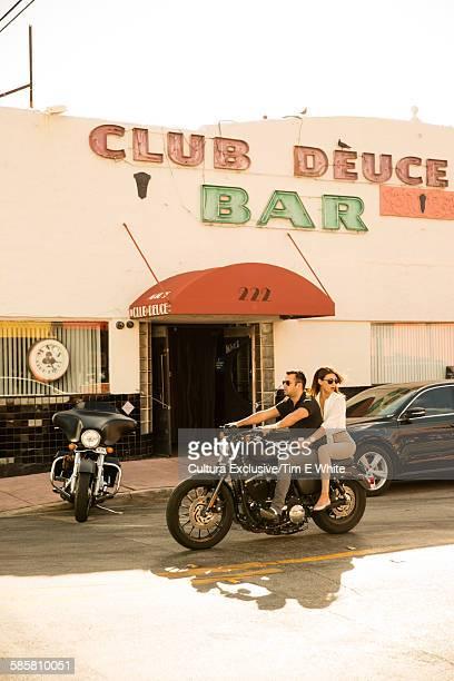 Side view of couple on motorbike, South Beach, Miami, Florida, USA