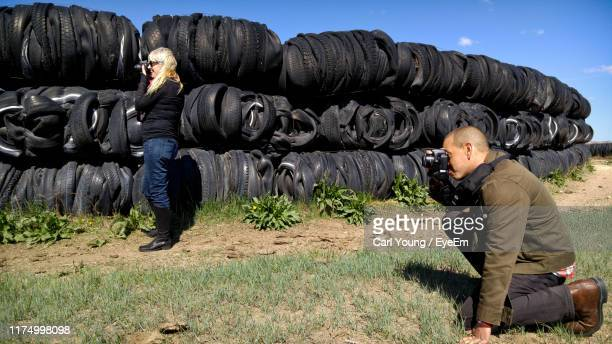 side view of couple photographing with cameras against stacked tires - partire bildbanksfoton och bilder