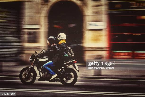 side view of couple riding motorcycle on street in city - moto photos et images de collection