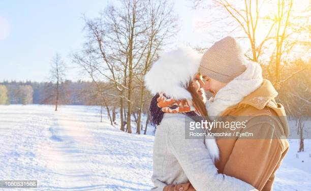 Side View Of Couple Romancing On Snow Covered Field