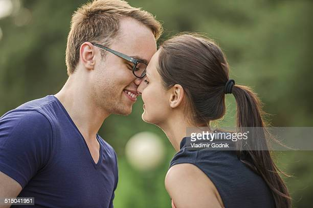 Side view of couple rubbing noses in park