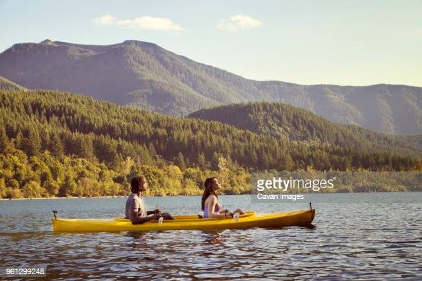 side view of couple sitting in canoe on river against mountain - rowing boat stock pictures, royalty-free photos & images