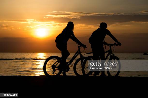 side view of couple standing on seashore with their bicycles and - ipek morel stock pictures, royalty-free photos & images