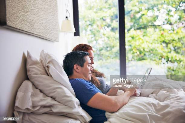 Side view of couple using tablet computer while lying on bed at home