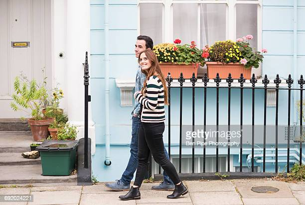 Side view of couple walking in street smiling