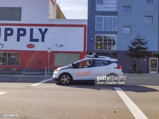 Side view of Cruise self driving car from General Motors with safety driver visible driving through downtown San Francisco California January 4 2019
