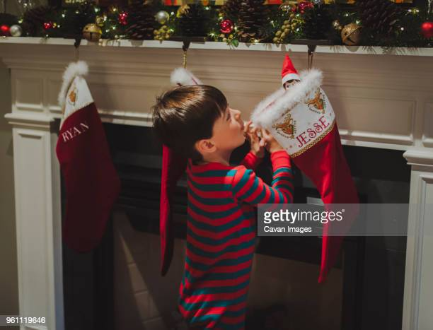 side view of curious boy looking at toy in sock hanging by fireplace during christmas - calza della befana foto e immagini stock