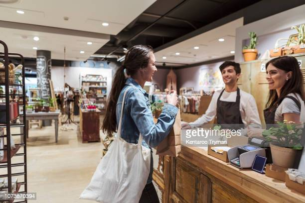side view of customer talking with male and female owners at store - happy merchant stock pictures, royalty-free photos & images