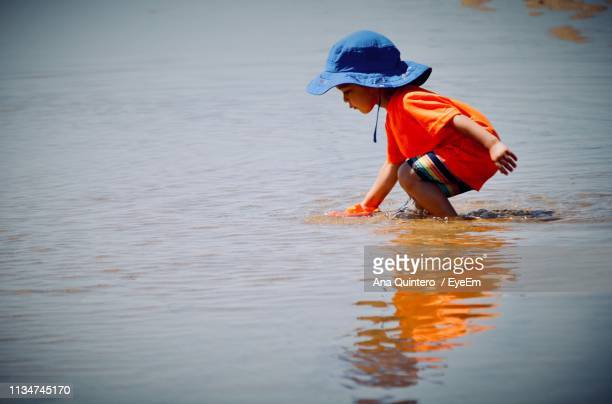 Side View Of Cute Boy Playing In Sea