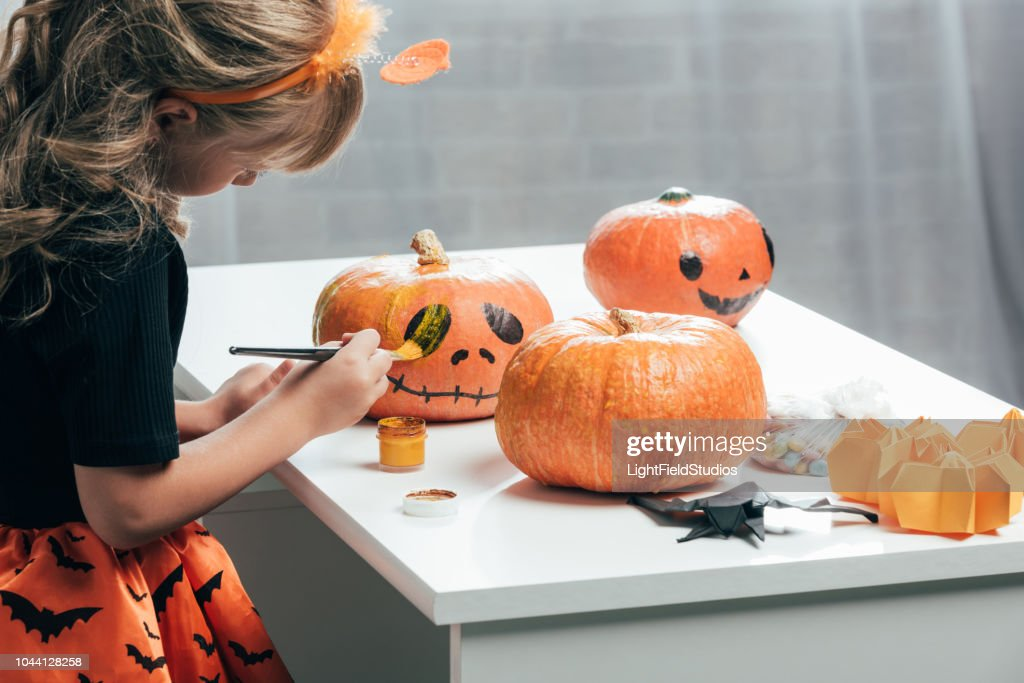 side view of cute child painting pumpkins for halloween at home : Stock Photo