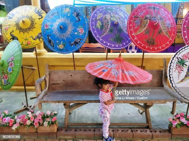 side view of cute girl holding umbrella on footpath - mae sot stock photos and pictures