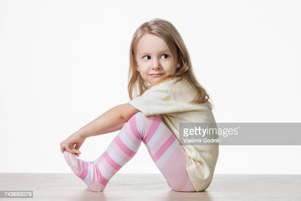 side view of cute girl sitting on floor against white background - 4 5 ans photos et images de collection