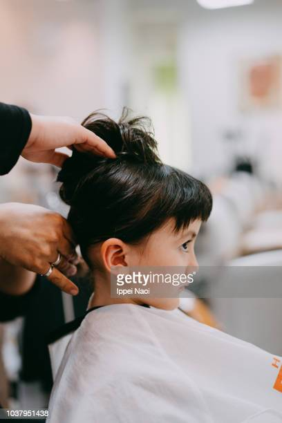 Side view of cute mixed race little girl at hairdresser