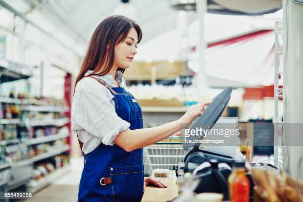 side view of deli owner using cash register in store - convenience store counter stock photos and pictures