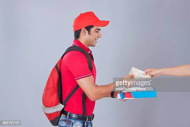 Side view of delivery man delivering pizza to customer against gray background