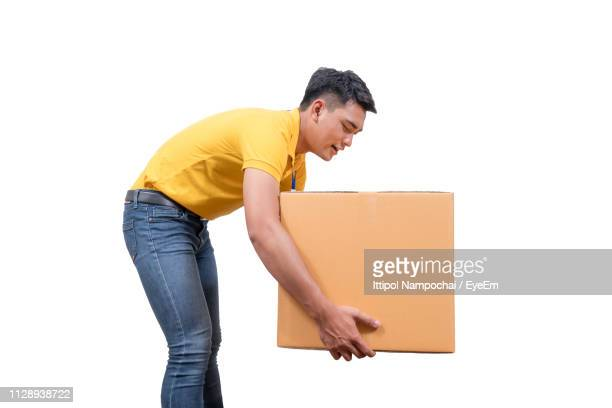 side view of delivery man holding package beige background - inarcare la schiena foto e immagini stock