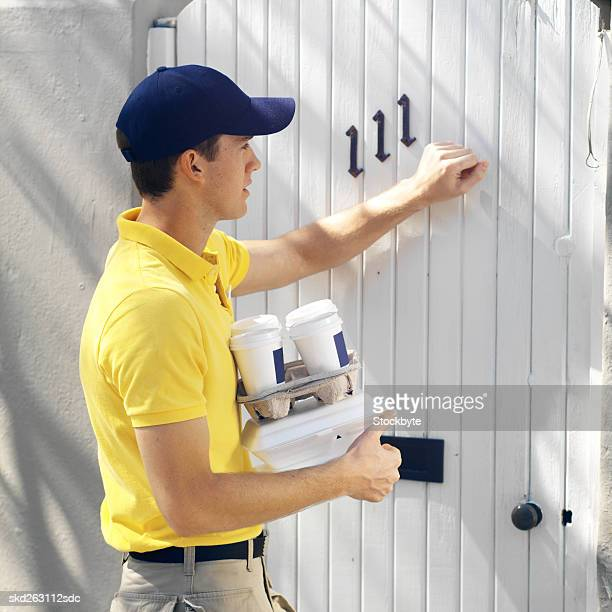 Side view of delivery man knocking on door and delivering fast food