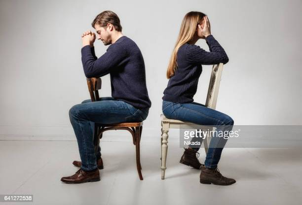 Side view of depressed couple sitting back to back on chairs