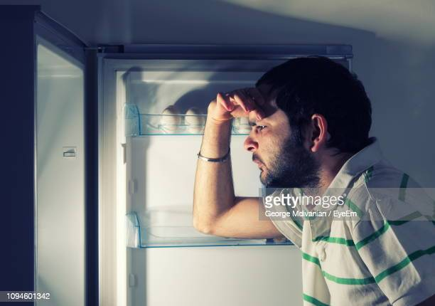 side view of depressed man looking in empty refrigerator at home - empty fridge stock pictures, royalty-free photos & images