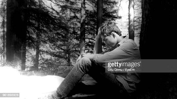 Side View Of Depressed Man Sitting At Forest