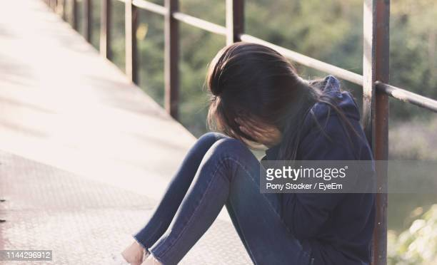 side view of depressed woman covering face while sitting on footbridge - suicidio fotografías e imágenes de stock