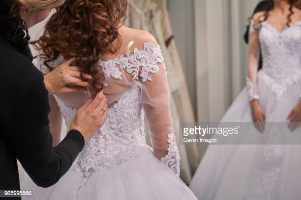 side view of designer assisting bride in trying wedding dress at store - robe photos et images de collection
