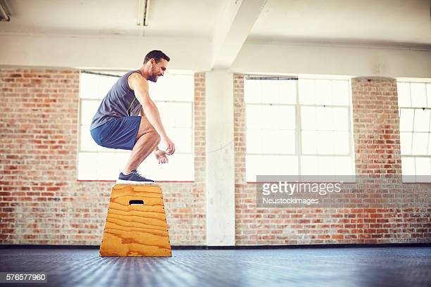 Side view of determined athlete box jumping in gym