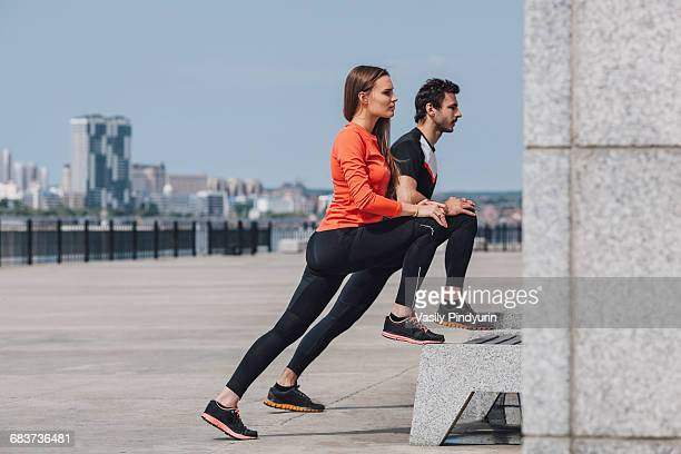 Side view of determined friends stretching legs while exercising on promenade