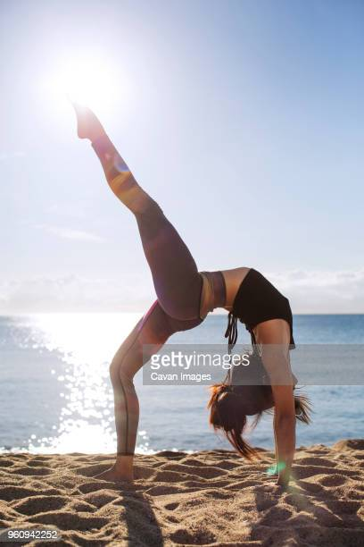 side view of determined woman doing backbend on beach - bending over backwards stock photos and pictures