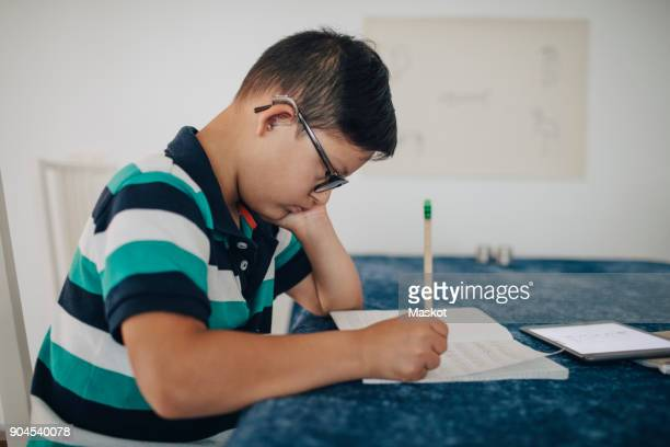 Side view of disabled boy writing on book while sitting at table