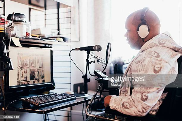 Side view of disabled man wearing headphones while looking at computer