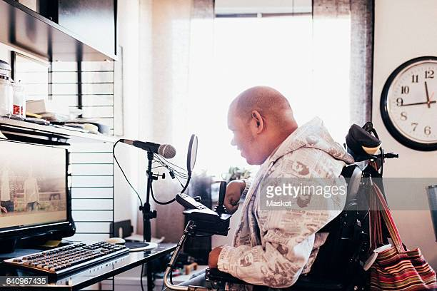 Side view of disabled musician in recording studio