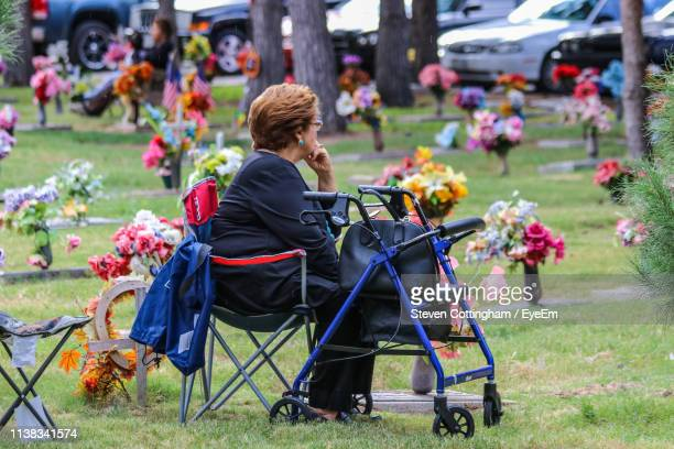 side view of disabled woman sitting on chair by mobility walker in park - steven cottingham stock-fotos und bilder