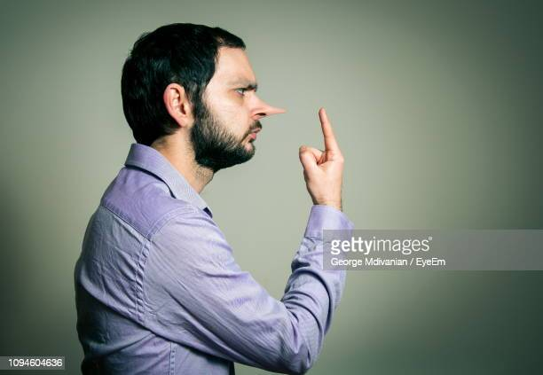 side view of dishonest mid adult man with long nose pointing against gray background - pinocchio stock pictures, royalty-free photos & images