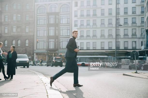 side view of entrepreneur walking on road against building in city - mensch im hintergrund stock-fotos und bilder