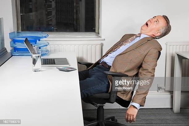 Side view of exhausted middle-aged businessman in front of laptop in office